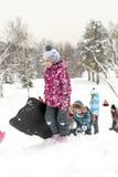 I bambini che fanno scorrere sulla neve fa scorrere nell'inverno russo Fotografia Stock