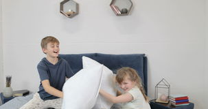 I bambini che hanno divertiresi nei genitori inseriscono i cuscini di combattimento, famiglia felice in camera da letto nella mat stock footage
