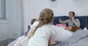 I bambini che hanno lotta di cuscini sui genitori inseriscono, divertimento felice della famiglia in camera da letto archivi video