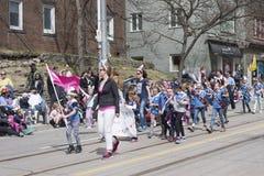 I bambini che indossano le orecchie del coniglietto marciano lungo la via della regina nel Beac Fotografie Stock