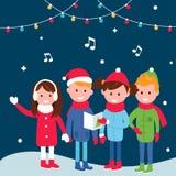 I bambini che portano i cappotti caldi dell'inverno cantano i canti natalizii sulla notte di Natale Immagine Stock