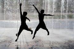 I bambini che saltano il gioco in fontana Immagine Stock