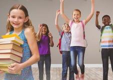 I bambini che saltano per la gioia nella sala con i libri Fotografie Stock Libere da Diritti