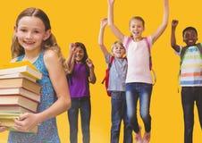 I bambini che saltano per la gioia nella sala con i libri ed il fondo giallo Immagine Stock Libera da Diritti