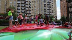 I bambini che saltano su un trampolino in un ` s dei bambini parcheggiano archivi video