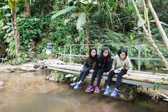 I bambini che si siedono sul ponte di legno dall'insenatura della montagna esaminano il pesce Fotografia Stock
