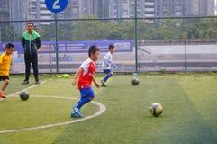 I bambini cinesi stanno preparando per giocar a calcioe immagine stock