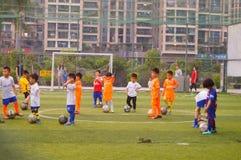 I bambini cinesi stanno preparando per giocar a calcioe fotografia stock