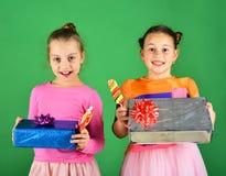I bambini con i fronti felici posano con le caramelle ed i presente Immagine Stock