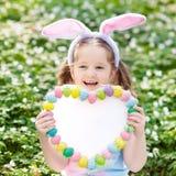 I bambini con le orecchie del coniglietto sull'uovo di Pasqua cercano immagine stock libera da diritti