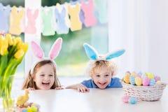 I bambini con le orecchie del coniglietto sull'uovo di Pasqua cercano Immagine Stock