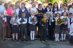 I bambini con i mazzi dei fiori si sono iscritti alla prima classe alla scuola all'inaugurazione dell'anno scolastico nel giorno  Fotografie Stock Libere da Diritti