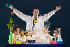 I bambini con professore pazzo che fa la scienza sperimenta in laboratorio immagini stock libere da diritti