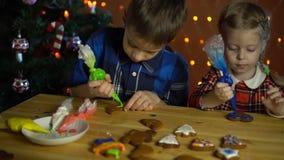 I bambini coprono di dolci variopinti di una glassa, accanto all'albero di Natale archivi video