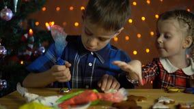 I bambini coprono di dolci variopinti di una glassa, accanto all'albero di Natale video d archivio