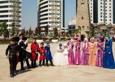 I bambini in costumi nazionali nel fiore parcheggiano Fotografia Stock