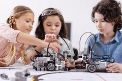 I bambini creativi che lavorano alla tecnologia proiettano alla scuola fotografia stock libera da diritti