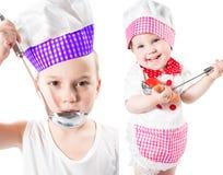 I bambini cucinano il ragazzo e la ragazza che portano un cappello del cuoco unico con la pentola isolata su fondo bianco. Fotografie Stock