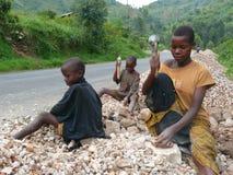 I bambini del Burundi rompono le rocce fotografia stock
