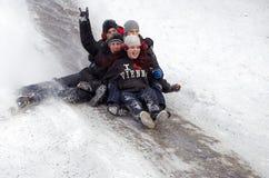 I bambini della gente guidano sulla neve dell'inverno che sledding dalle colline Inverno che gioca, divertimento, neve Fotografie Stock