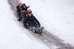 I bambini della gente guidano sulla neve dell'inverno che sledding dalle colline Inverno che gioca, divertimento, neve Fotografia Stock