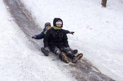 I bambini della gente guidano sulla neve dell'inverno che sledding dalle colline Inverno che gioca, divertimento, neve Immagini Stock