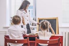 I bambini della ragazza e del ragazzo con l'insegnante nella scuola ha un felice Fotografie Stock Libere da Diritti