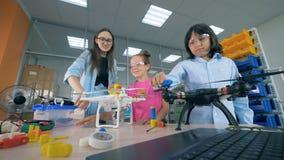I bambini della scuola esplorano i fuchi, elicotteri alla classe della tecnologia stock footage