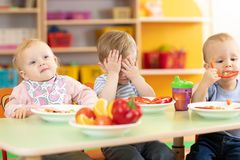 I bambini della scuola materna pranzano nell'asilo Il bambino rifiuta di mangiare immagine stock