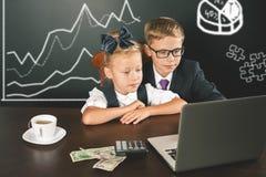 I bambini di affari utilizza un computer portatile Diagramma di affari, grafico Fotografia Stock