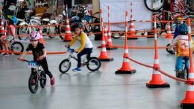 I bambini di 4-6 anni stanno correndo sulle biciclette durante la mostra 2017 del parco di Velo stock footage
