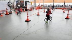 I bambini di 4-6 anni stanno correndo sulle biciclette durante la mostra 2017 del parco di Velo archivi video