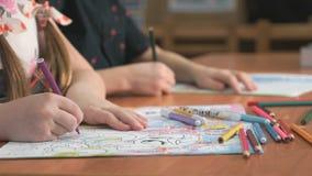 I bambini disegna le immagini facendo uso delle matite in album stock footage