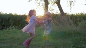 I bambini divertendosi il ragazzino e la ragazza all'aperto e svegli stanno girando su erba verde archivi video