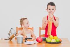 I bambini divertenti della famiglia felice stanno preparando la torta di mele, su un fondo bianco Fotografia Stock Libera da Diritti