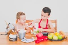 I bambini divertenti della famiglia felice stanno preparando la torta di mele, su un fondo bianco Immagini Stock