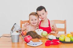 I bambini divertenti della famiglia felice stanno preparando la torta di mele, su un fondo bianco Fotografia Stock