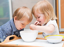 I bambini divertenti stanno mangiando il dessert Fotografia Stock