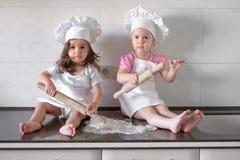 I bambini divertenti stanno preparando la pasta nella cucina Famiglia felice fotografia stock libera da diritti