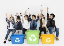 I bambini e la plastica imbottiglia un recipiente di riciclaggio Immagine Stock