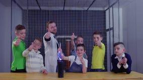 I bambini e le manifestazioni dell'insegnante sfoglia sulla tenuta del globo di vetro sopra la bobina di Tesla stock footage