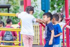 I bambini ed il genitore stanno avendo buon tempo nel campo da giuoco del parco di Kowloon fotografie stock libere da diritti