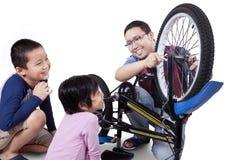 I bambini ed il loro papà riparano una bicicletta immagine stock libera da diritti