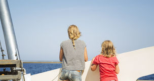 I bambini esaminano il mare dalla piattaforma di una barca Fotografia Stock