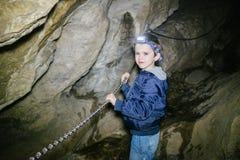 I bambini esplorano la caverna sotterranea immagine stock