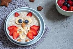 I bambini fanno colazione porridge della farina d'avena con le bacche ed i dadi immagine stock libera da diritti