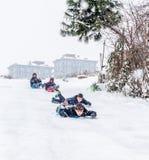 I bambini fanno scorrere su neve con il sacchetto di plastica a Costantinopoli Immagine Stock