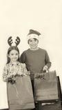 I bambini felici che indossano il Natale vestono i regali della tenuta, isolati su wh Fotografia Stock