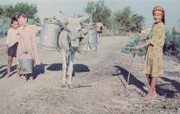 I bambini felici consegnano l'acqua dal fiume al loro terreno coltivabile Immagini Stock