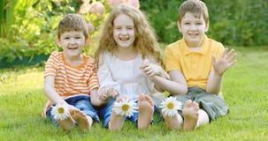 I bambini felici degli amici con la margherita fiorisce ad erba verde video d archivio